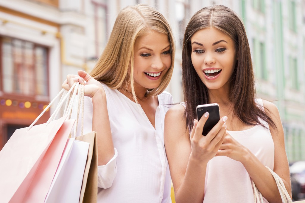 Can you imagine that? Two surprised young women holding shopping bags and looking at mobile phone together while standing outdoors