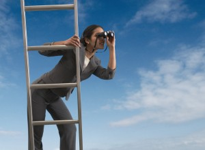 Businesswoman standing on a ladder looking through binoculars